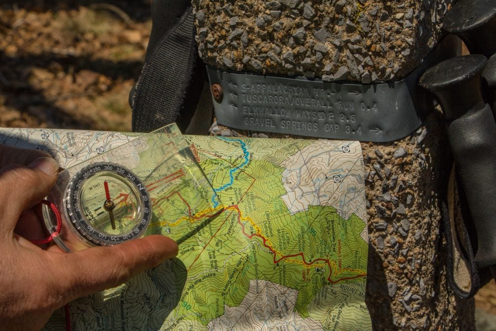 close up view of a hiker holding a compass over their map beside Appalachian trail marker
