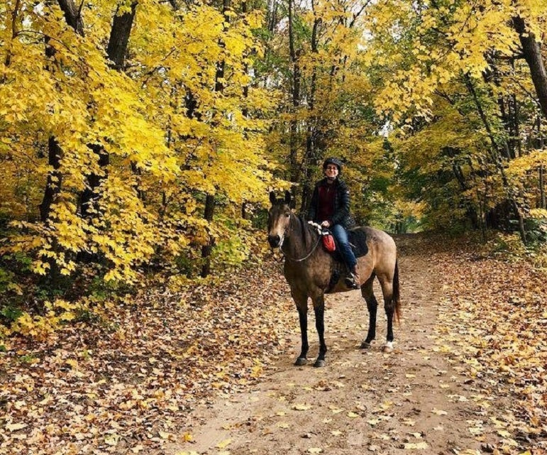 woman on horse in forest of yellow Fall foliage