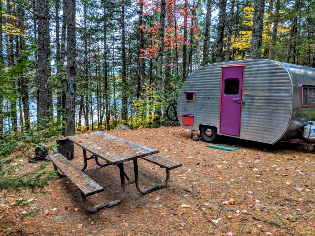 vintage camper trailer in wooded autumn campsite