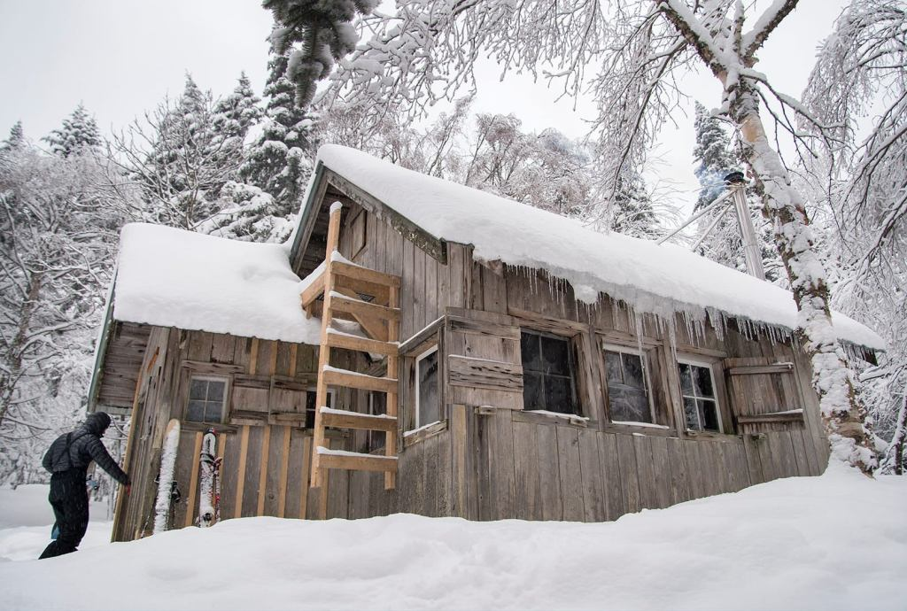 a wooden vermont camping cabin covered in snow during the day