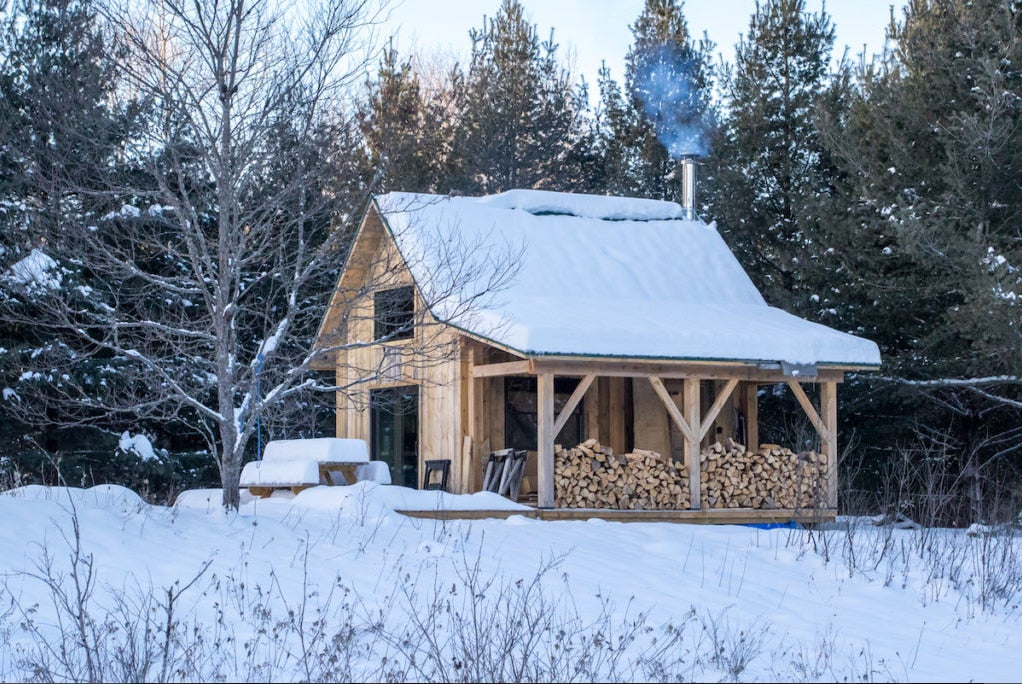 a log cabin in vermont covered in snow