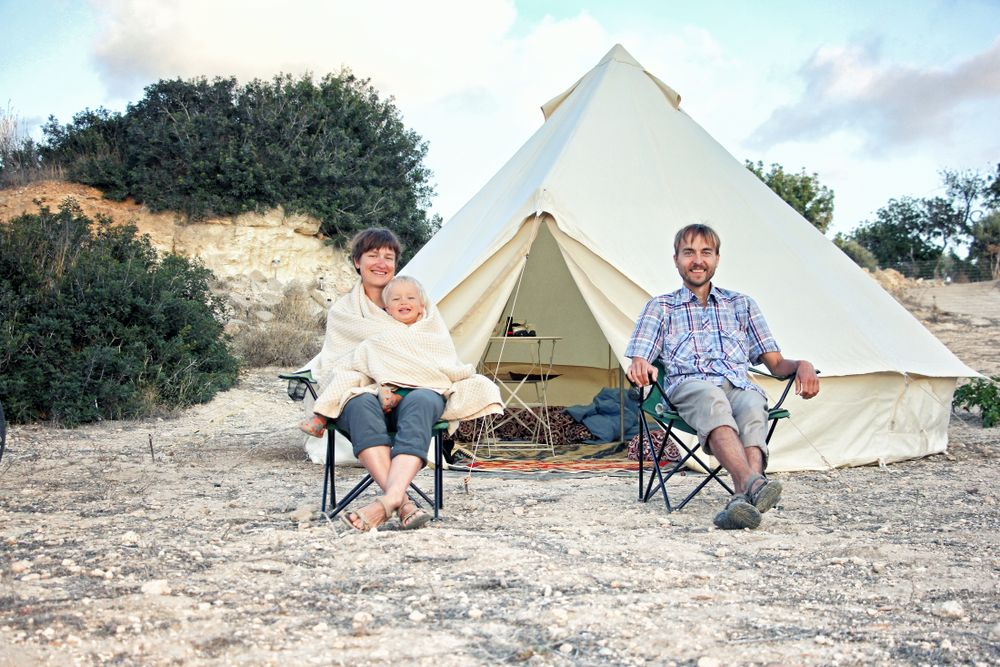 family of 3 sit outside their canvas yurt glamping tent surrounded by limestone and shrubs
