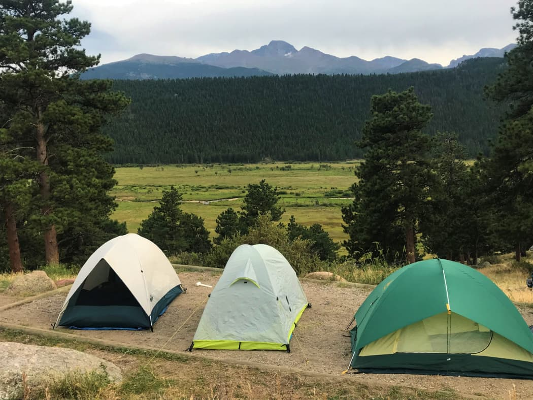 3 small tents on tent pad overlooking pine trees and valley with mountains in the distance