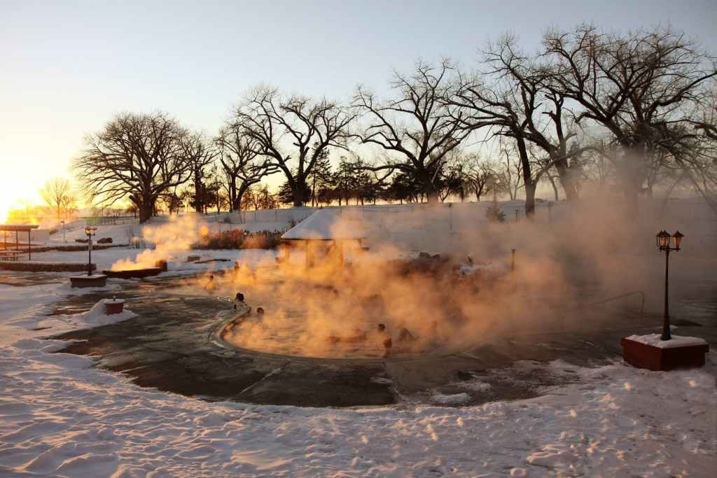 a snowy winter scene at sunset in Utah while people soak in steaming hot springs on the ground