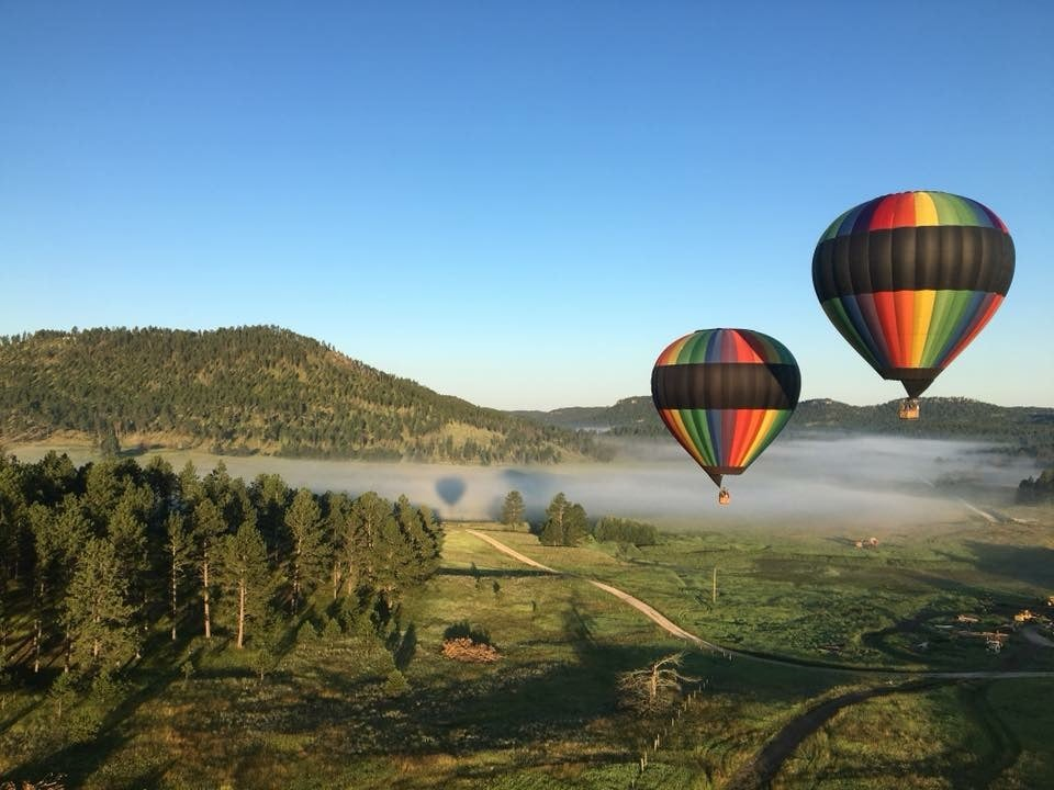 A panoramic photo of two air balloons over the Black Hills of South Dakota