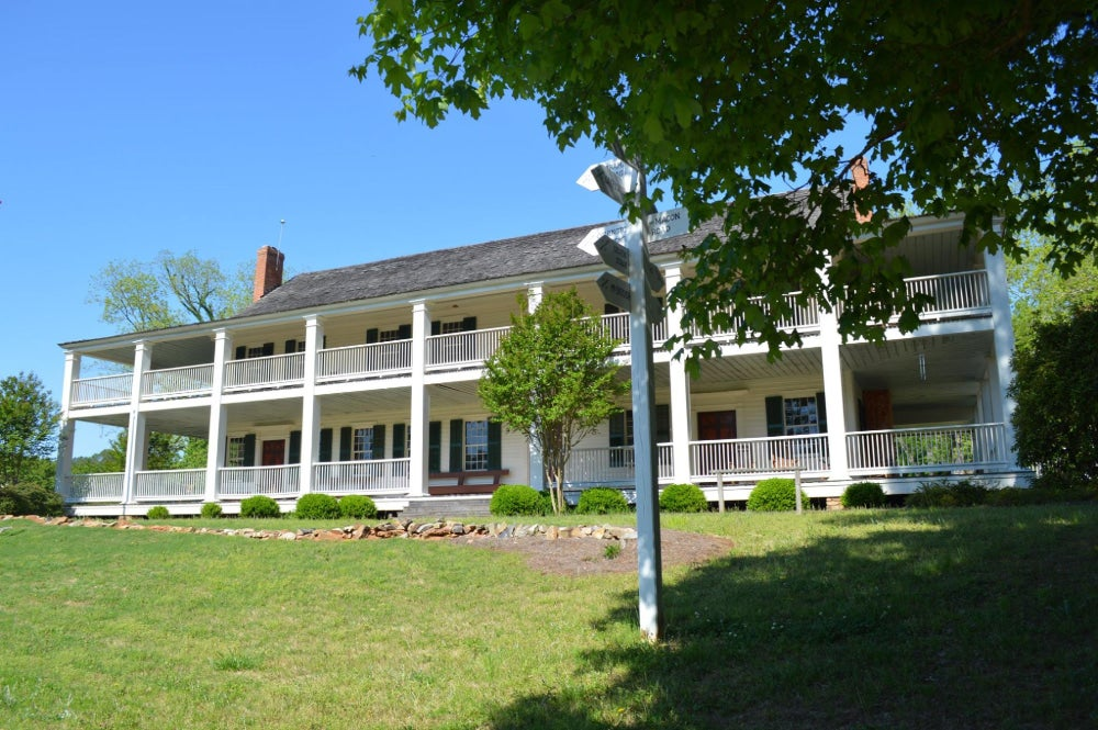 The Indian Springs Hotel & Museum with white beams and walls and gray roof