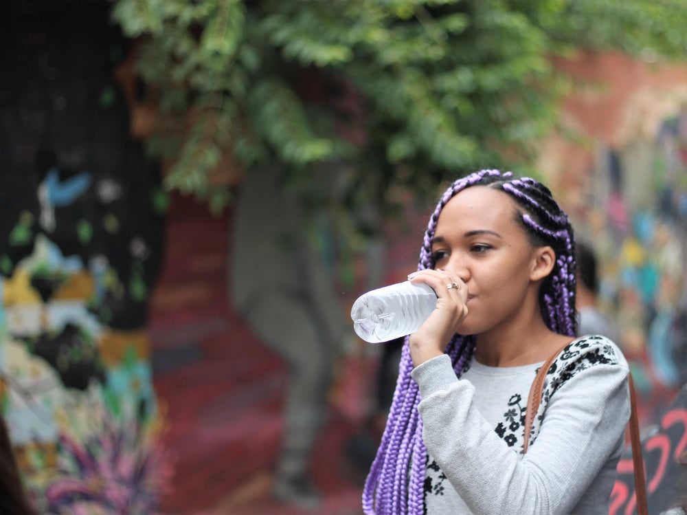 Woman wearing gray shirt and purple braids drinks water from water bottle, with trees and colorful walls in the background