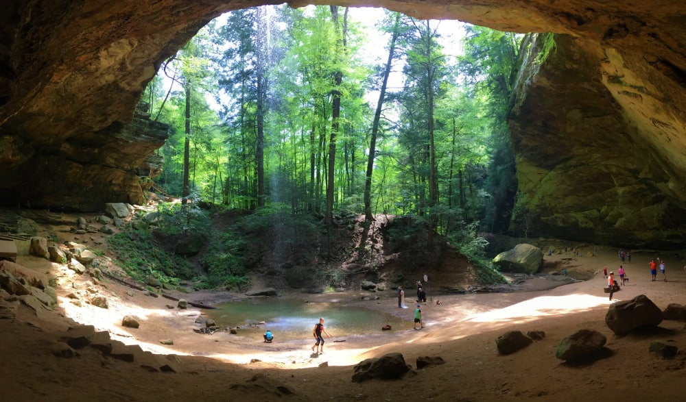 visitors scattered around waterfall visible from inside a large cave in hocking hills state park