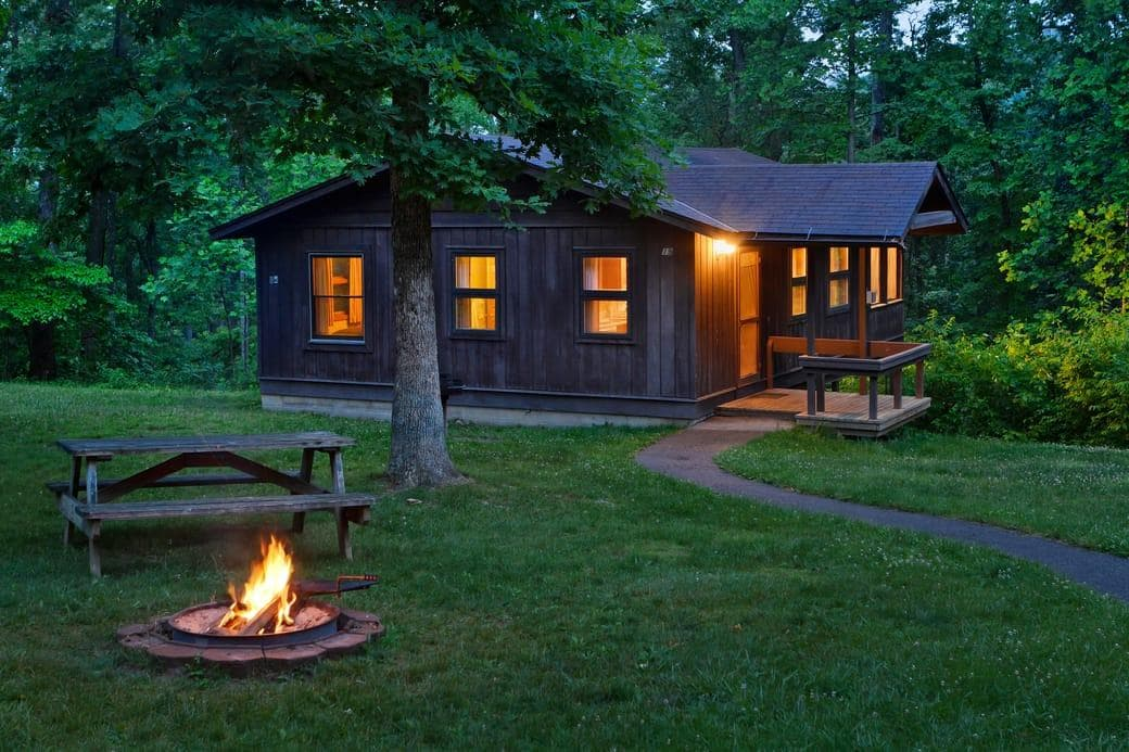 picnic table near firepit with fire burning and warm light coming from the windows of a brown log cabin at dusk by forest