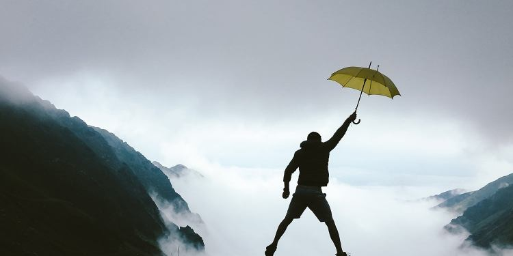 hiker in midair holding a yellow umbrella