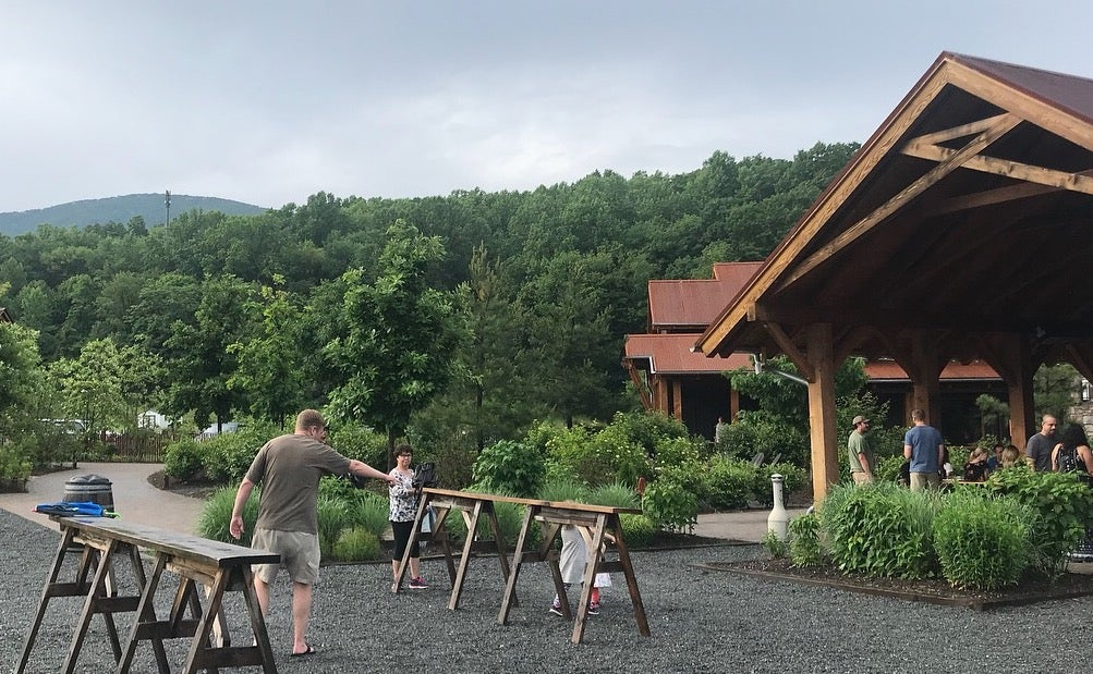 Landscape shot of people at Devil's Backbone Brewery with trees in background