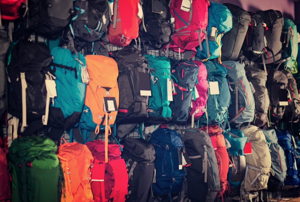 Rows of hanging backpacking backpacks in a a variety of colors including orange, red, blue, black, green, and grey.
