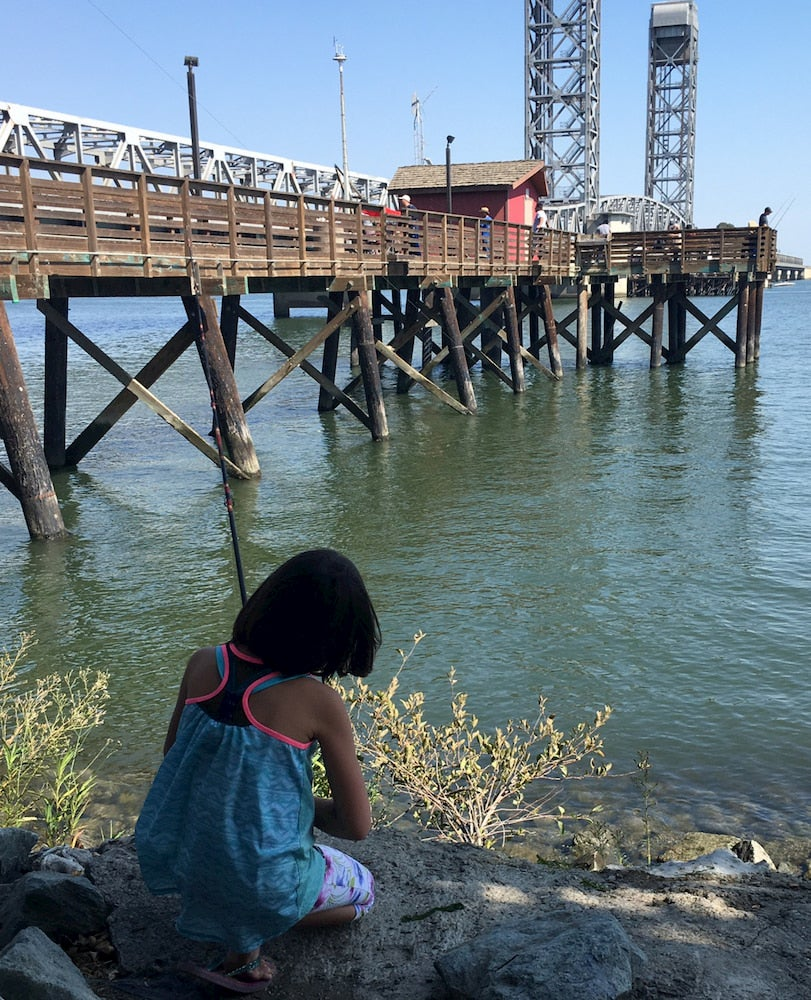 Young girl fishing along river with boardwalk in background