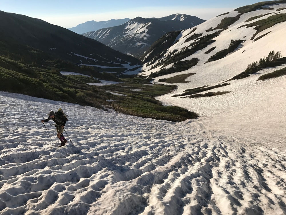 Man hiking up snowfield with valley and mountains behind him