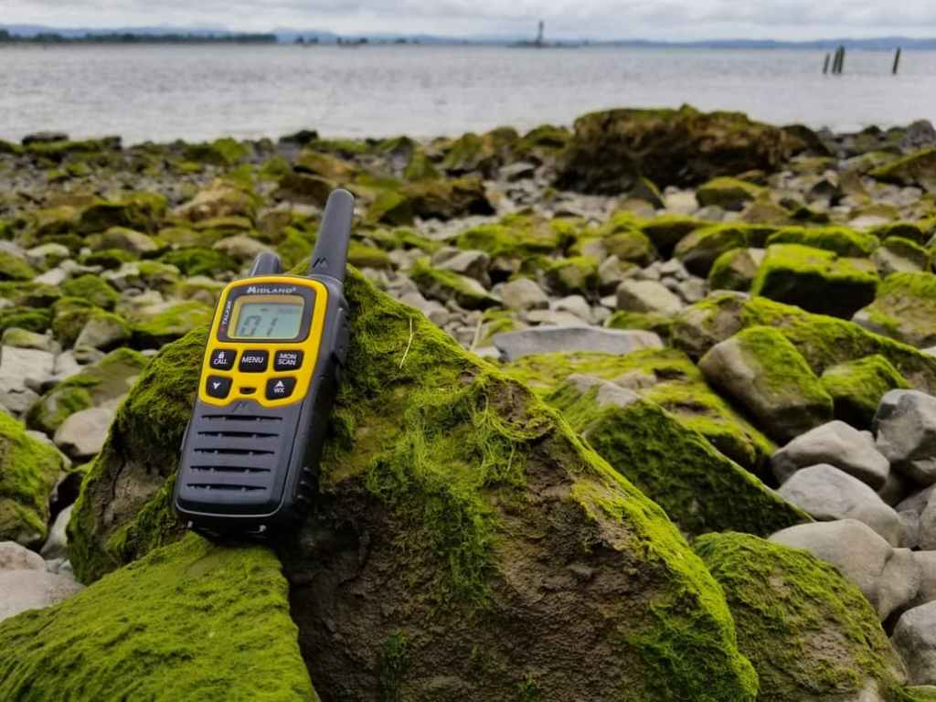 yellow walkie talkie on moss covered rocks on shore of river in the background