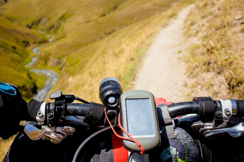 The handlebars of a bike packed with gear and a gps on a mountain trail.