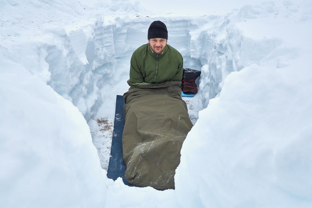 Man sleeping in dugout hole in snow.