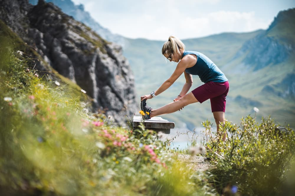 Female hiker stretching her legs in the mountains.