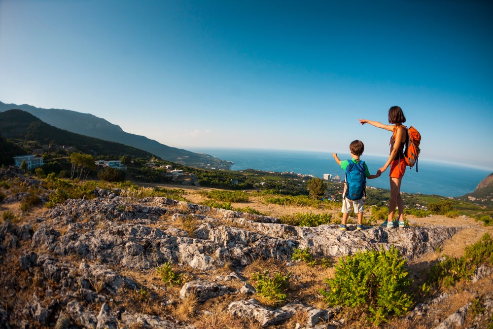 Mother and child hold hands while stopping to admire a coastal viewpoint during a hike.