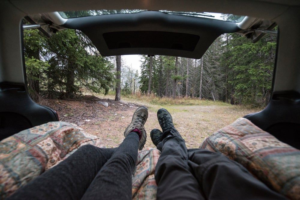 Couple sitting on a mattress in the back of a car in a forest with their feet sticking out.