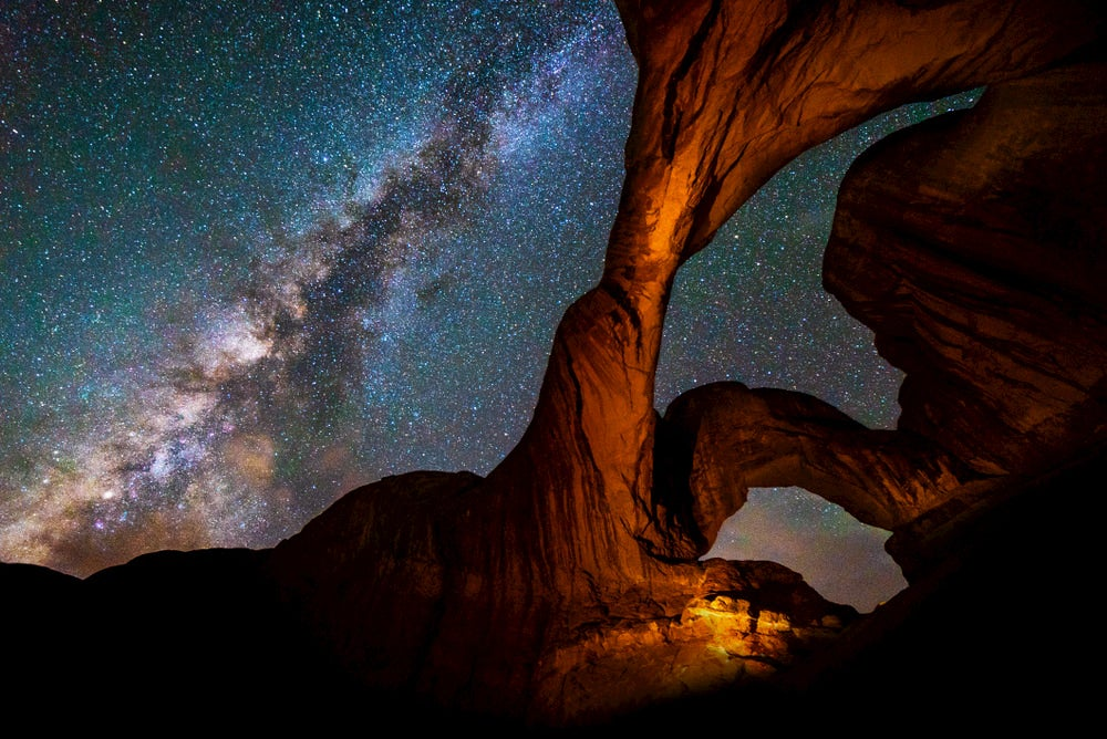 Twisting red rock arches in Moab, utah with the milky way seen in the sky in the background