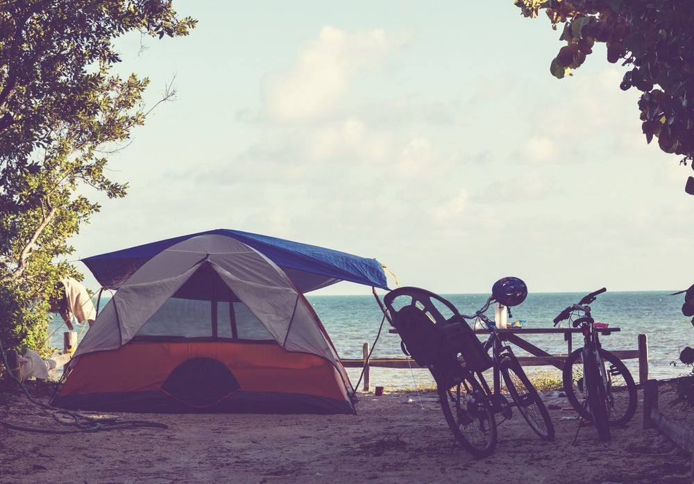 oceanfront campsite with a tent setup besides bike resting on a picnic table