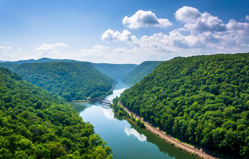 Landscape view of the New River Gorge with reflective river and green trees beside river