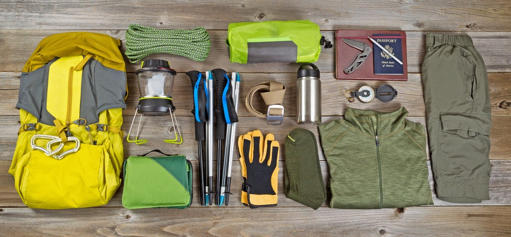 Backpacking gear spread on the floor including backpack, gloves, trekking poles, etc.