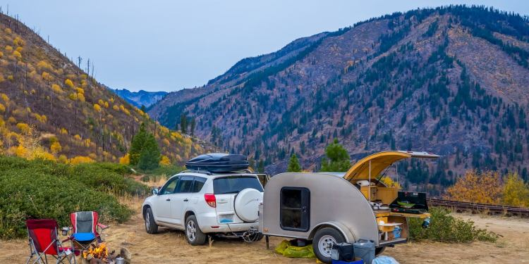 Small SUV towing a teardrop trailer parked in the mountains on a dirt road at a campsite.