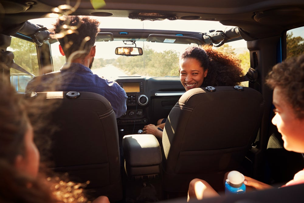 Family of four in car on a road trip with mom looking back and smiling