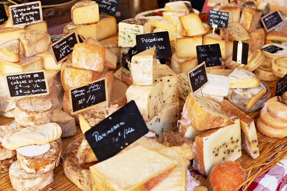 A variety of cheeses laid out at a market