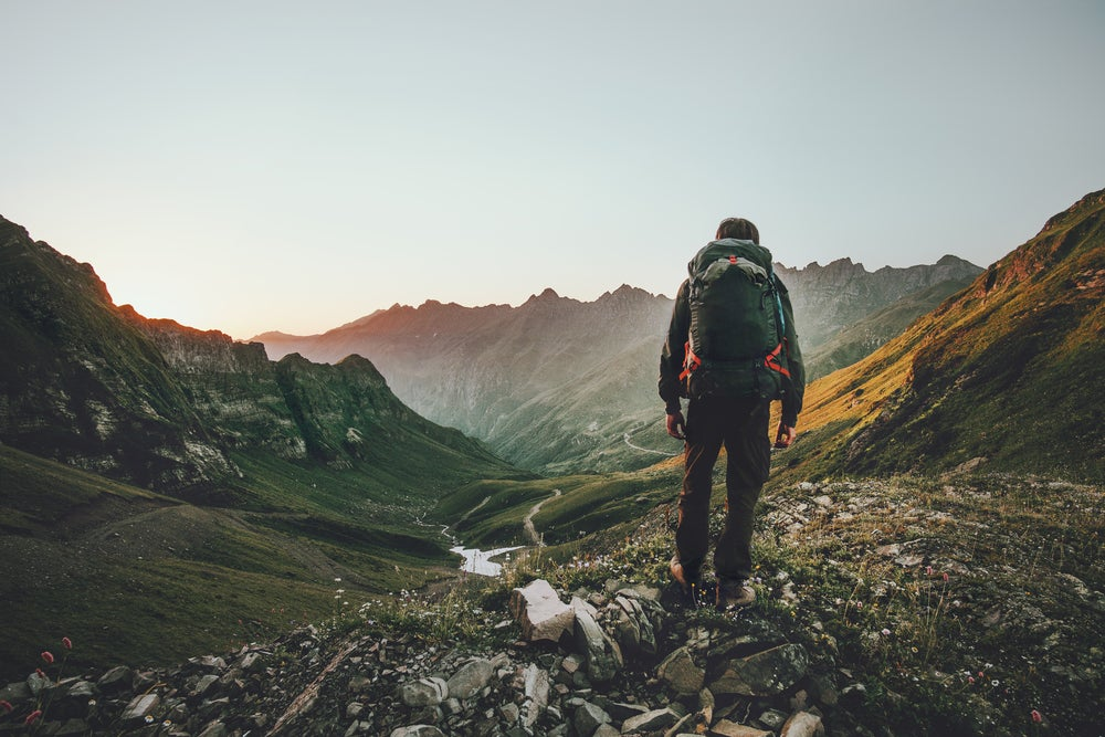 Man backpacking through a mountain valley in the fog at dusk.