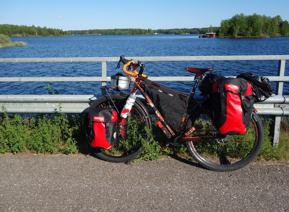 a bikepacking rig on a bike with saddlebags on a bike path in front of a lake