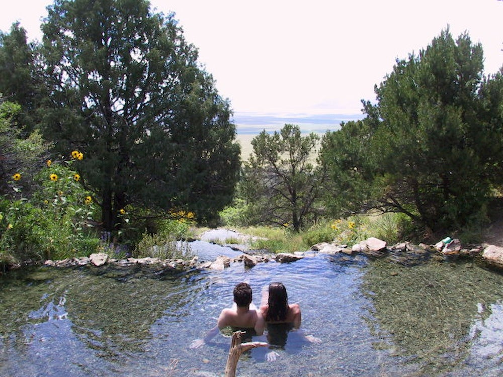 A couple in the nude bathing in the hot springs.