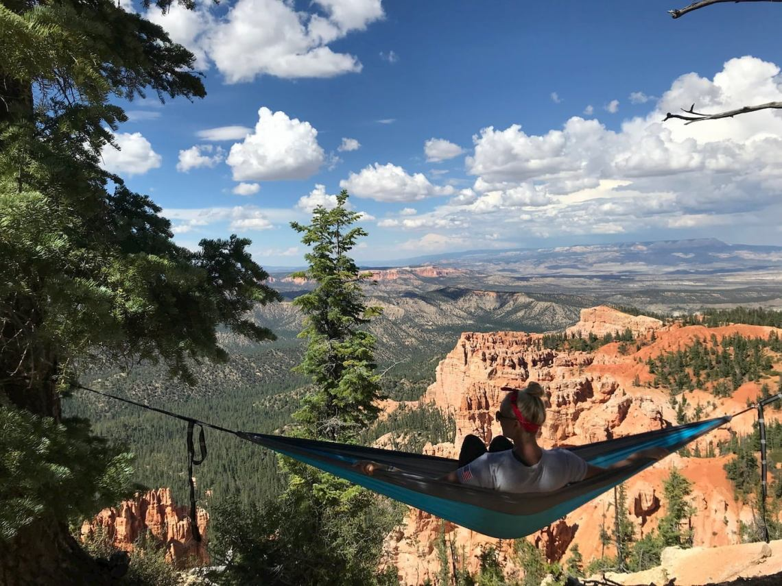 Girl hanging in hammock over sunset canyon.