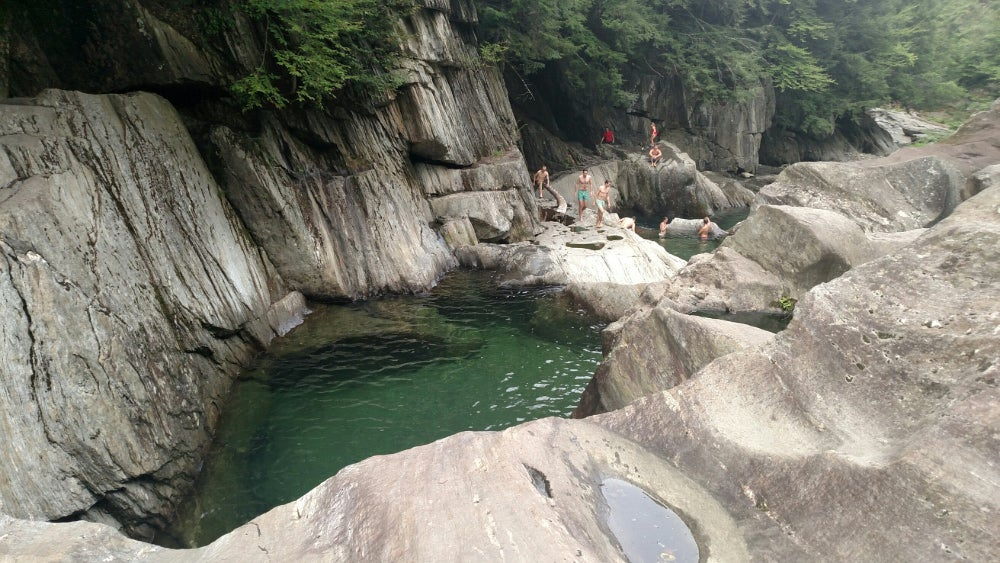 Large, smooth boulders surround a swimming hole at warren falls with swimmers in the background