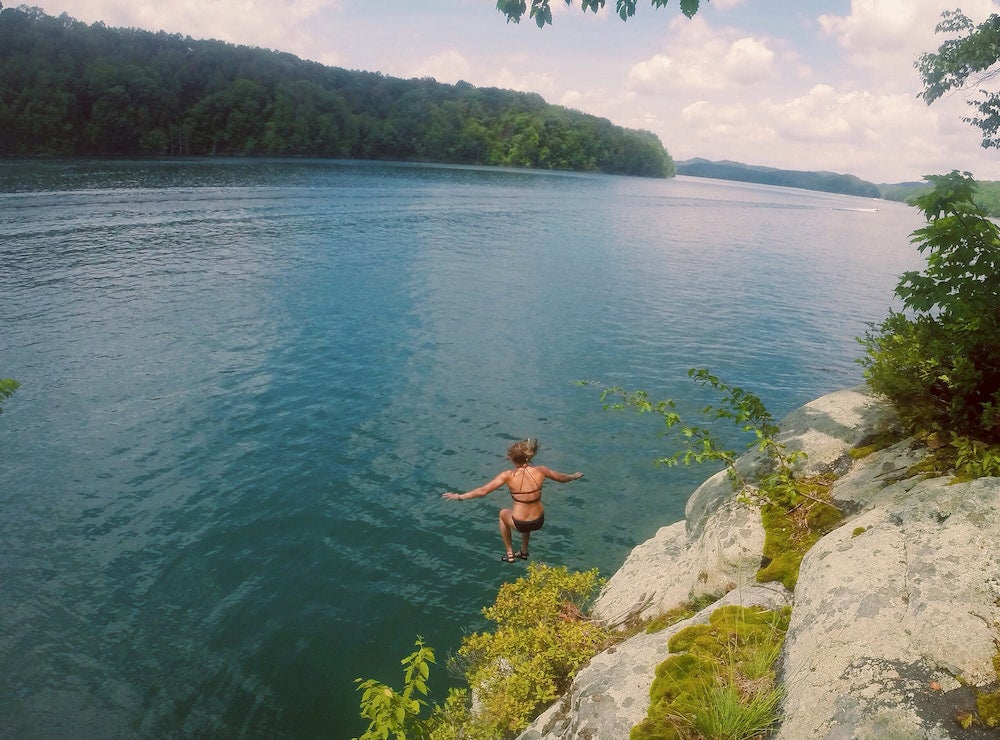 Woman cliff jumping from rocks into river