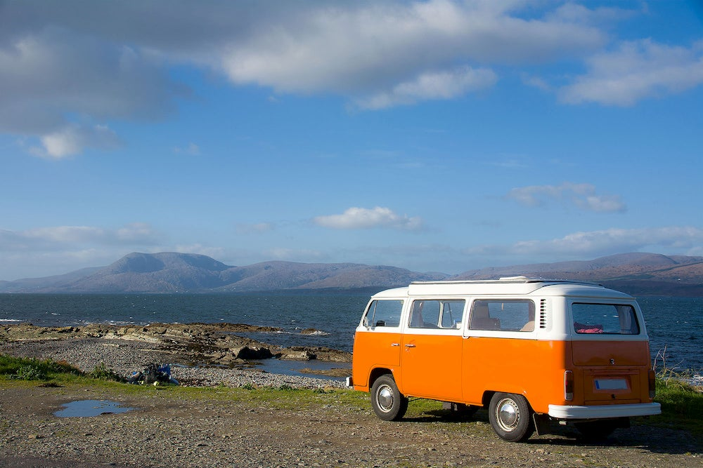a volkswagon camper van parked on the shore of the ocean