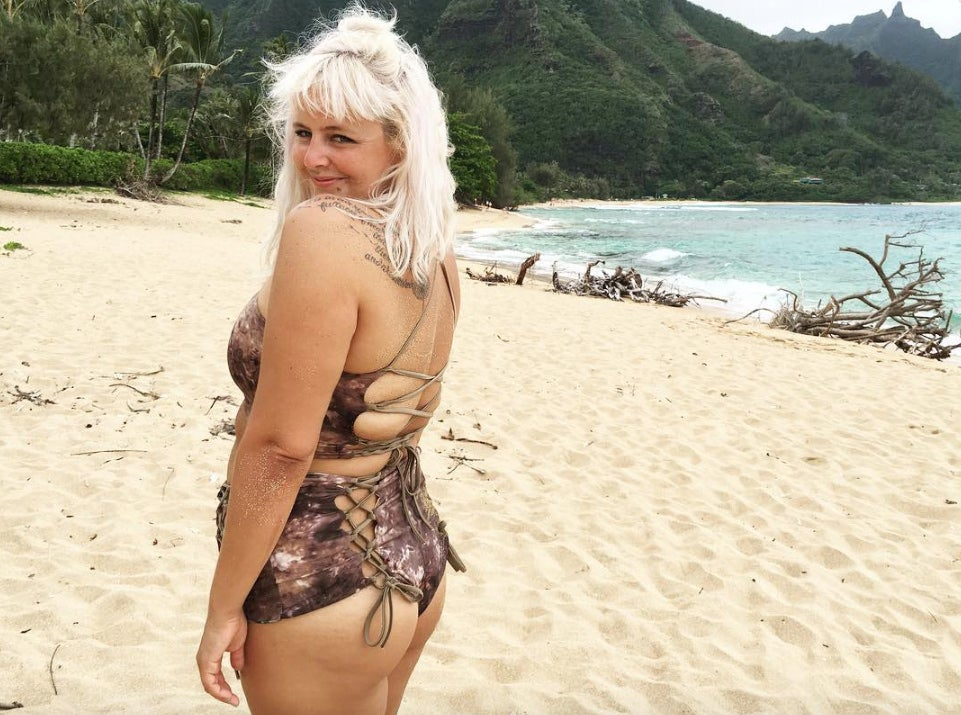 a woman wearing a custom bathing suit smiles at the camera standing on a beach