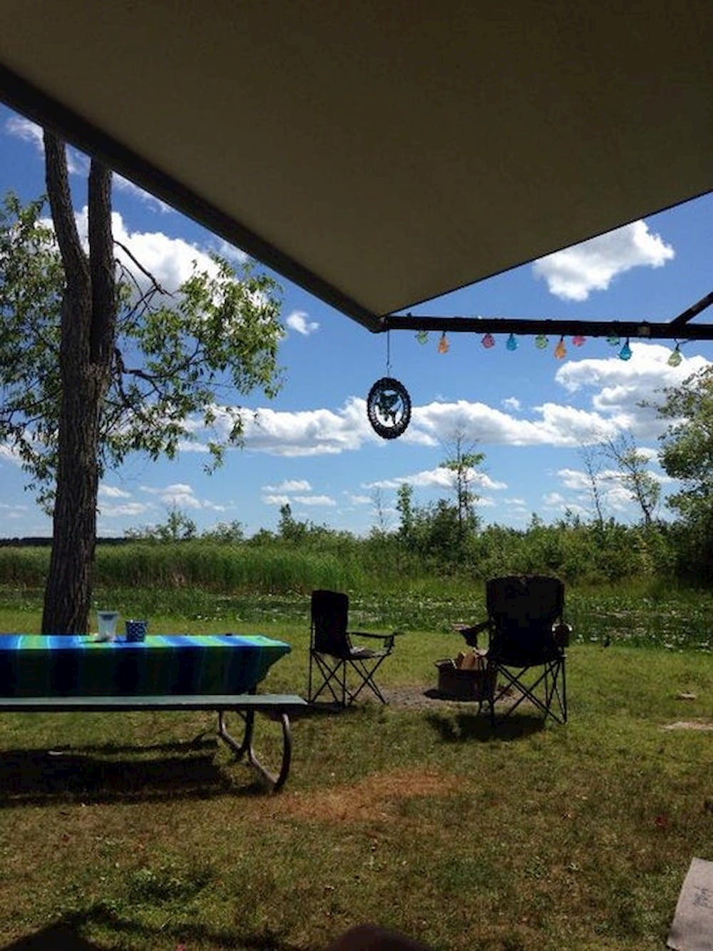 Picnic table and RV awning at a field campground.