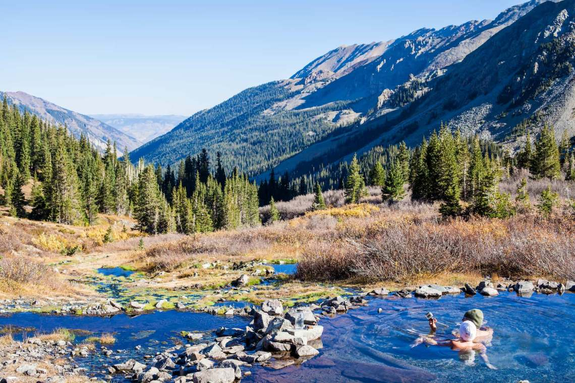 Panoramic view of mountains and couple in hot spring
