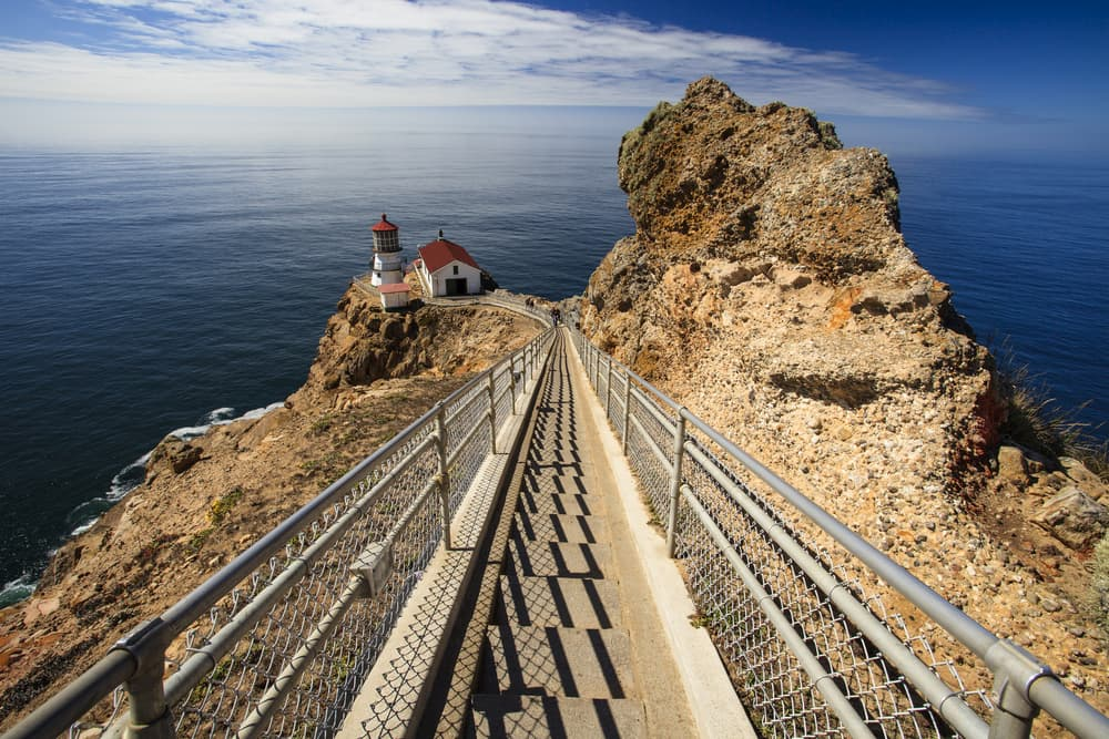 looking down staircase toward Point Reyes lighthouse perched on rocky outcropping in the pacific ocean