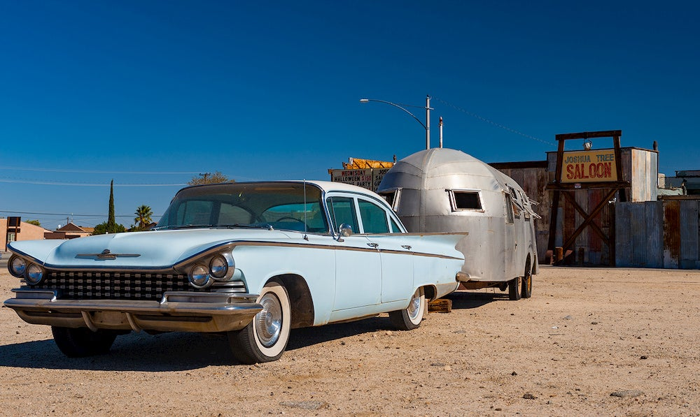 a vintage car towing an airstream trailer in the desert