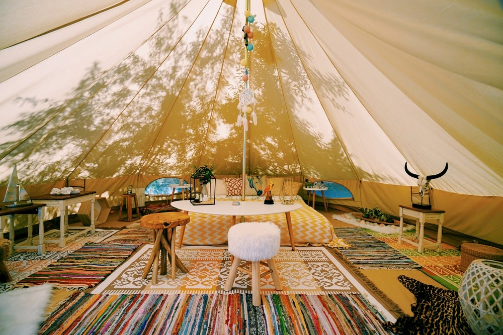 Large tent with colorful carpets and fuzzy chairs with tree silhouette in background