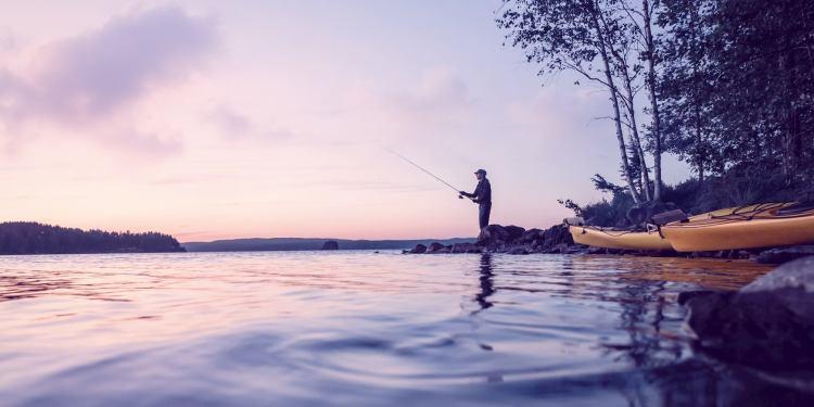 Fisherman at dusk on a lake next to kayaks.