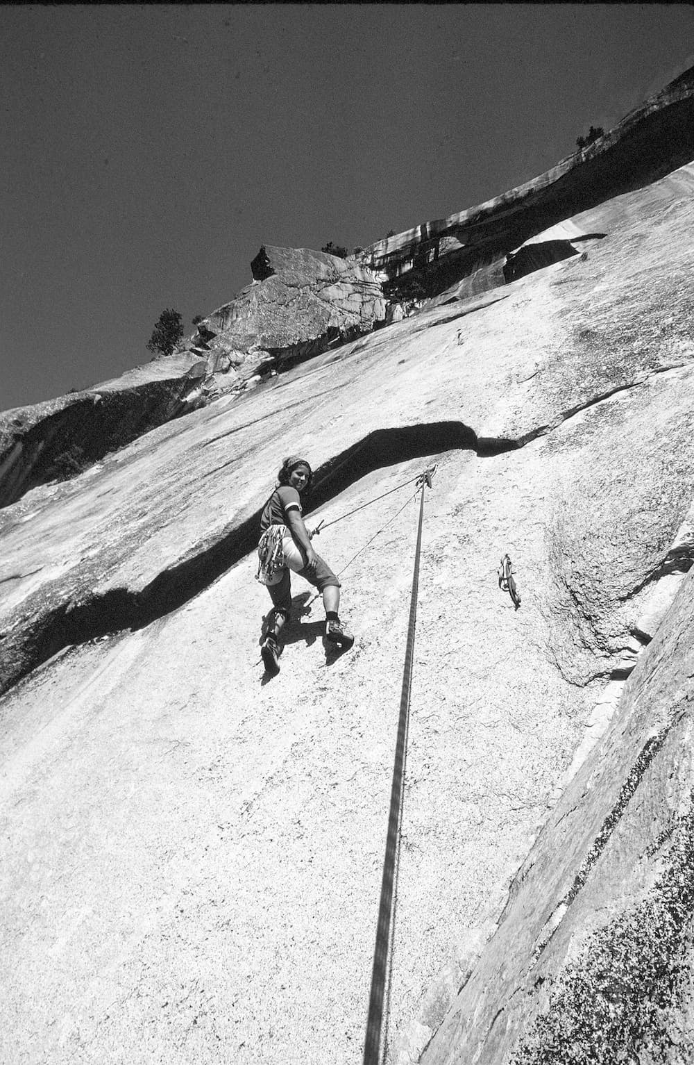 a woman climbing with a rope up a sheer rock face looking down at the camera