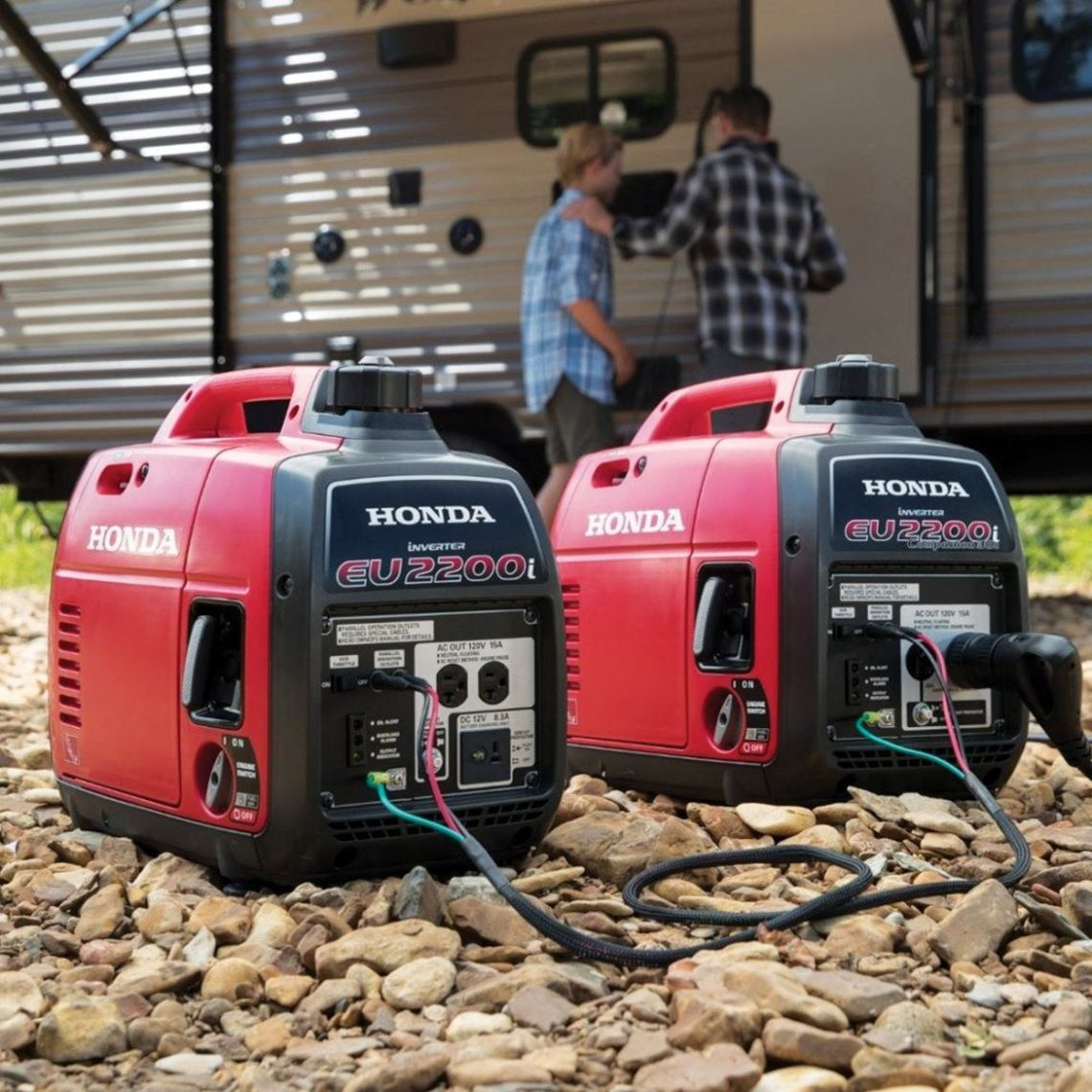 two portable generators on the ground near an RV