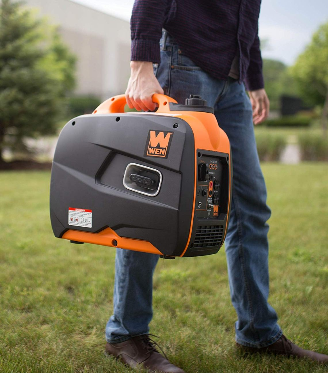 a man holding a portable camping generator in one hand