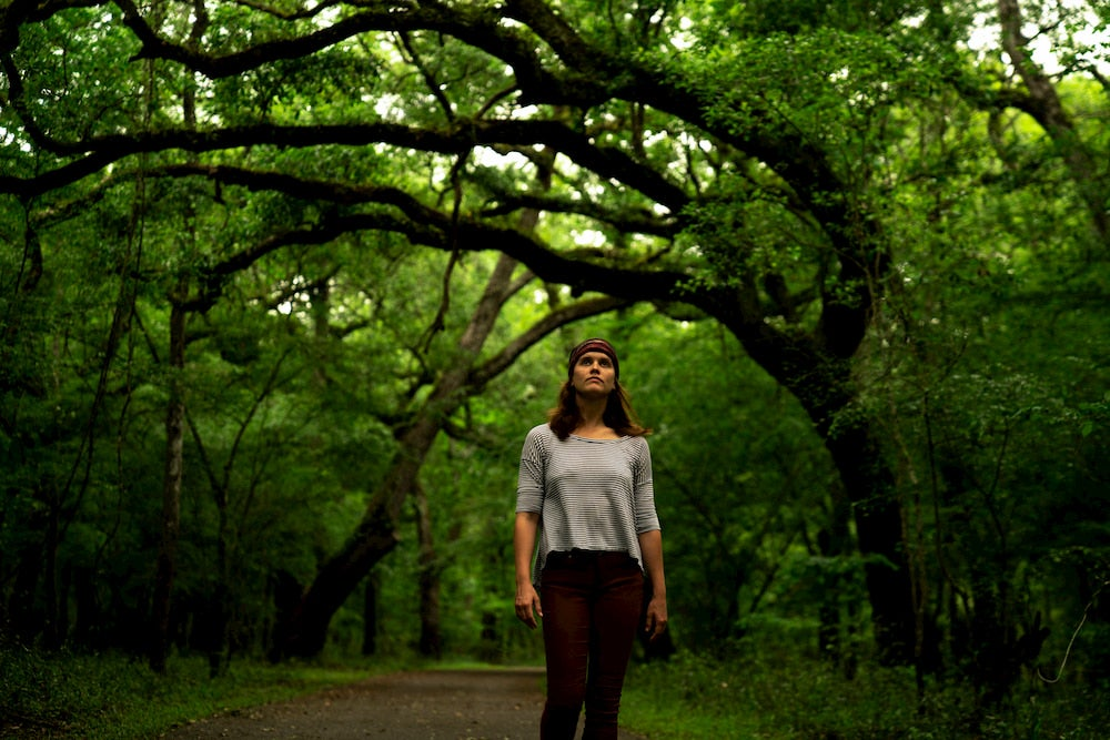 a woman stands on a tree lined hiking trail