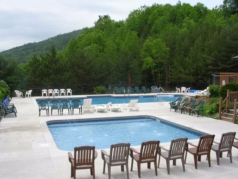 a row of pool chairs in front of two pools near a line of trees